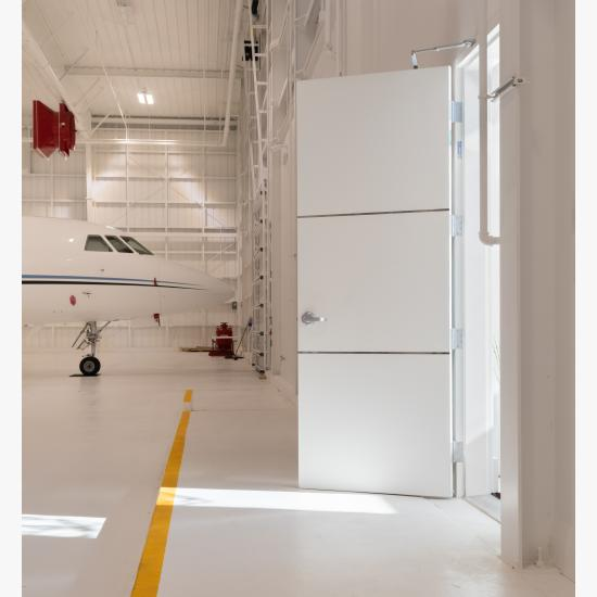 """The lounge of this this private jet hangar features TMIR3000 doors in MDF with ½"""" bright stainless steel inlays."""