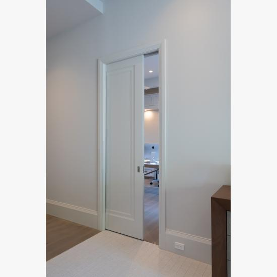 A TS1000 pocket door, in MDF with Miracle (MR) moulding and flat (C) panel, opens from the master bedroom to a private office.