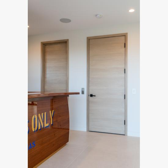 An upstairs lounge features TMF1000 flush doors in quarter sawn white oak with a custom ceruse finish.