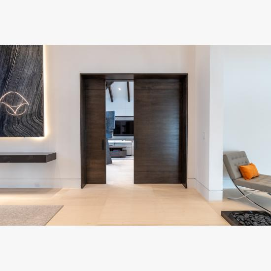 """A pair of TMIR3080 pocket doors, in quarter sawn white oak with ¼"""" kerf cut reveals, open to a family room. Builder provided stain finish."""