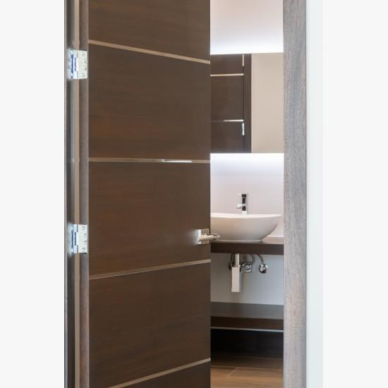 "An attached bathroom features TMIR6000 doors in mahogany with ½"" bright stainless steel inlay. Builder provided stain finish."